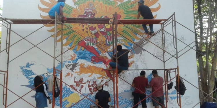 . Komunitas Seni Lukis Batuan, mengerjakan dinding mural utama. Mereka melukis Garuda.
