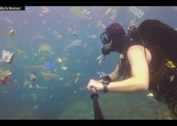 Sumber: https://www.mongabay.co.id/ Penyelam asal Inggris, Rich Horner menyelam di antara lautan sampah di Nusa Penida, Bali yang diunggah di akun facebooknya pada 3 Maret 2018. Foto : screenshot YouTube The Guardian.