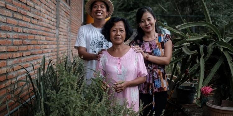Penulis berpose bersama keluarga di sela tanaman pangan di halaman rumah