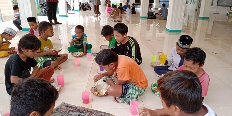 Anak-anak menikamti makanan gratis dari Warung MJ dalam masjid di Singaraja